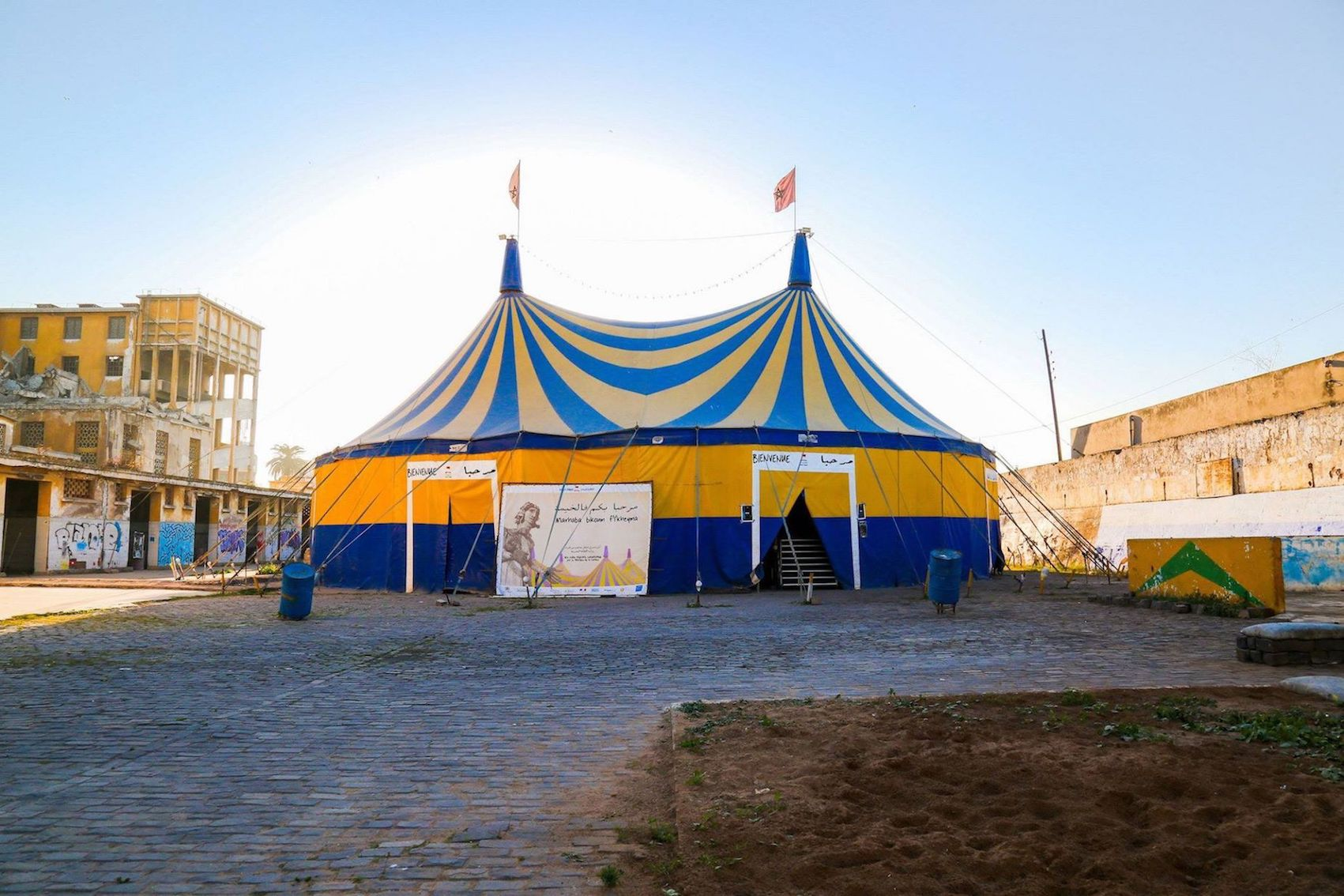 Théâtre Nomade's tent is staked among the cobblestones between the railroad tracks and the remaining buildings of Les Anciens Abattoirs, an abandoned slaughterhouse complex in the working-class neighborhood of Hay Mohammadi in Casablanca.