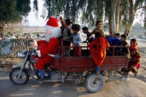 A man in a Santa Claus outfit touring a popular neighborhood on the outskirts of the Iraqi central city of Najaf takes children on a ride in a tuktuk on December 25 2018. AFP