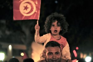 A little girl waives a Tunisian flag as a crowd gathers on Tunis main avenue Sunday Oct. 13 2019 AP Photo Hassene Dridi