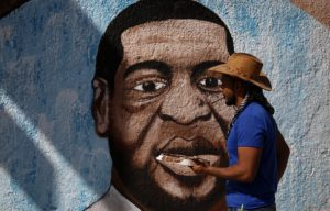 A Palestinian artist paints a mural depicting George Floyd a black American who died after being restrained by police officers in Gaza City Tuesday June 16 2020. AP Photo Hatem Moussa
