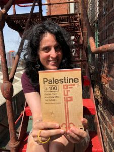 Basma Ghalayini holding her book Palestine 100 Stories from a century after the Nakba