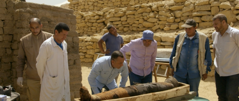 Members of the Egyptian excavation team examine one of the coffins found at the Saqqara archaeological site. Netflix Photo